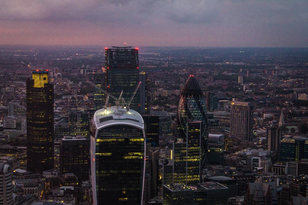 Blick auf mehrere Londoner Hochhäuser am Abend
