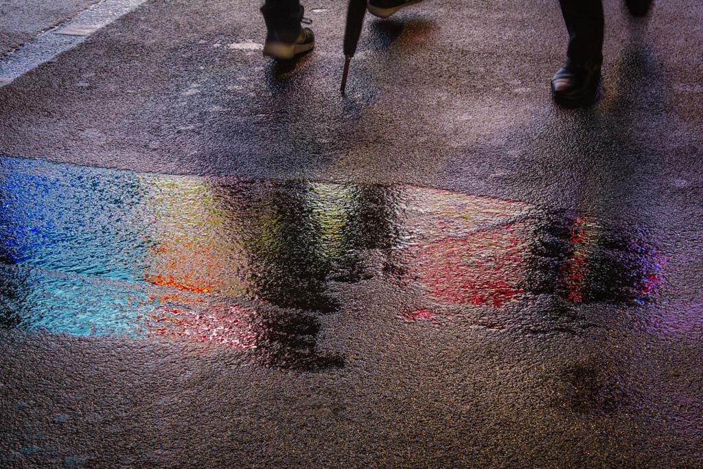Die farbigen Bildschirme am Piccadilly Circus spiegeln sich im nassen Asphalt