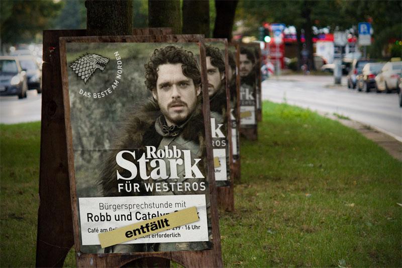 Zahlreiche Plakate mit der Aufschrift Robb Stark für Westeros, der Hinweis auf einer Bürgersprechstunde ist mit einem Entfällt-Hinweis überklebt