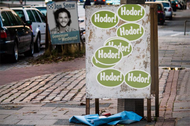 Abgerissenes Plakat, auf dem sich zahlreiche Hodor-Aufkleber befinden