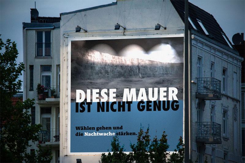 Wandplakatfläche mit dem Text: Diese Mauer ist nicht genug. Wählen gehen und die Nachtwache stärken